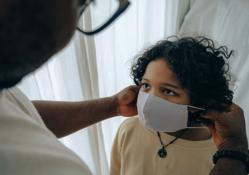 Crop man putting medical mask on face of ethnic child Free Stock Photo