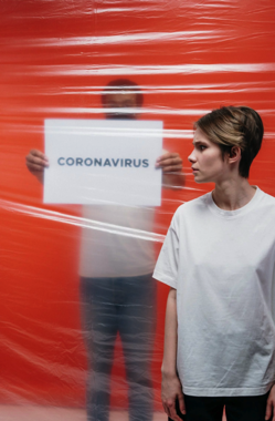 Woman With A Stressful Look At A Man Holding A Poster With Coronavirus Text Free Stock Photo